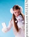 Woman with little snowman taking selfie photo. 65153276