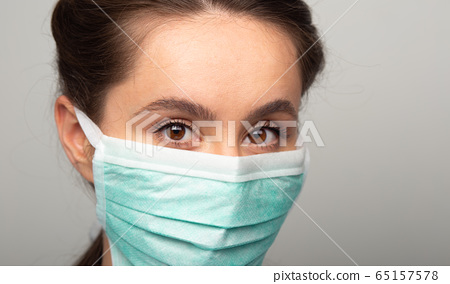 woman in surgical mask facing camera, wearing protective filter to prevent coronavirus infection, airborne respiratory illness such as flu, 2019-nCoV, ebola. studio shot isolated on white background 65157578