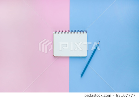 Spiral notebook or sketchbook on pink and blue background with copy space 65167777
