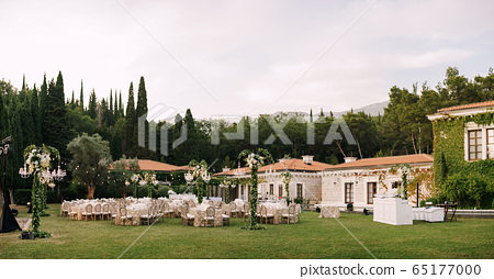 Wedding dinner table reception. Elegant tables for guests with cream tablecloths with patterns, on green lawn, with garlands and chandeliers hanging over them. Chairs with round back 65177000