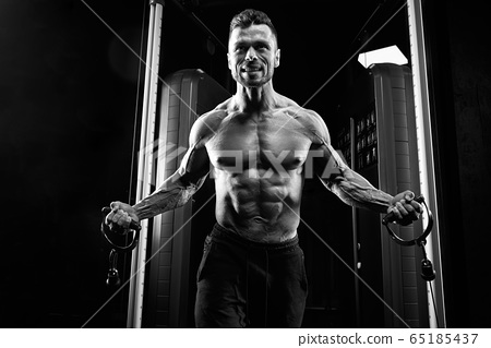 Shirtless sportsman doing crossover chest exercise. 65185437