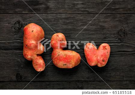 Ugly vegetables on a black wooden background. 65185518