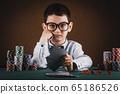 Little kid boy playing poker in a casino. 65186526