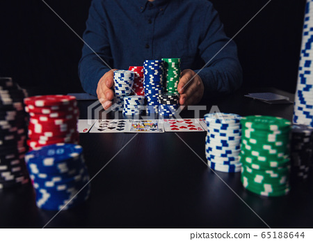 Risky guy poker player going all-in pushing his 65188644