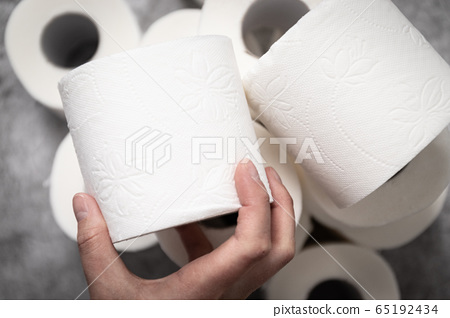 A female hand takes a roll of toilet paper for its intended use. 65192434