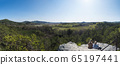 two woman sitting at sandstone rock viewpoint Havrani skaly, spring landscape in Lusatian Mountains , green hills, fresh deciduous and spruce tree forest. Blue sky background, copy space, Panoramic 65197441