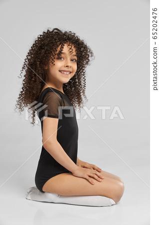 Little female gymnast sitting on studio floor. 65202476