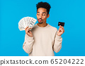 Modern lifestyle, business and finance concept. Cheerful happy african-american guy thinking how waste money, kissing cash dollars and holding credit card, winning prize, stading blue background 65204222