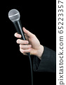 Close up of man's hand holding microphone isolated 65223357