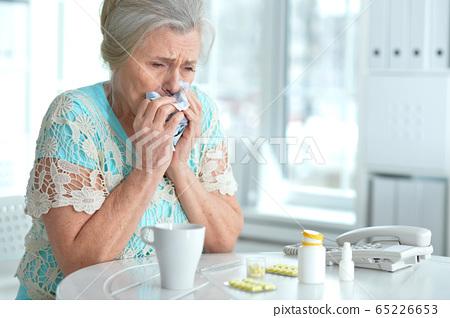 Sad sick senior woman sitting at table 65226653