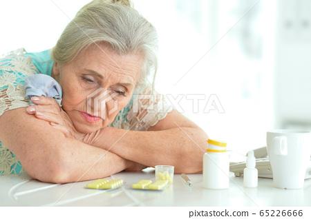 Sad sick senior woman sitting at table 65226666