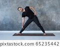 Sporty young man practicing yoga, doing stretching exercise, extended triangle pose 65235442