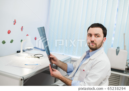 hospital doctor holding patient's x-ray film and mri, looking away 65238294