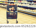 Beautiful baby in shopping cart - trolley. A trolley with products in which the child sits. Full cart with food in the supermarket. In the cart sits a baby. toned 65262226
