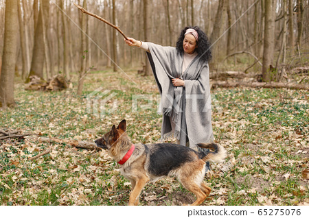 Adult woman in a spring forest with dog 65275076