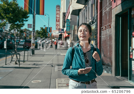 Smiling woman backpacker using phone searching 65286796