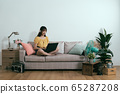 asian girl slacking off using laptop and earphones 65287208