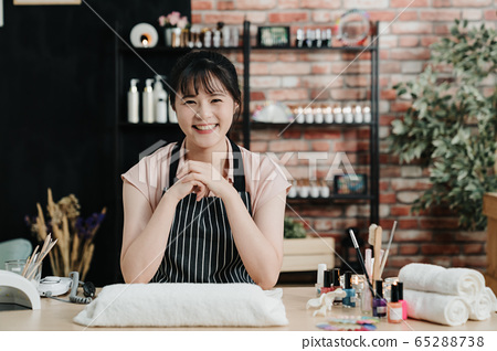 Portrait of happy professional nail master sitting 65288738