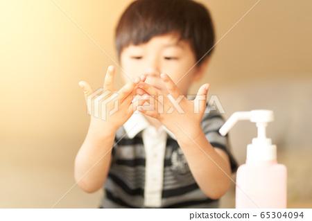 Boys sanitizing hands 65304094