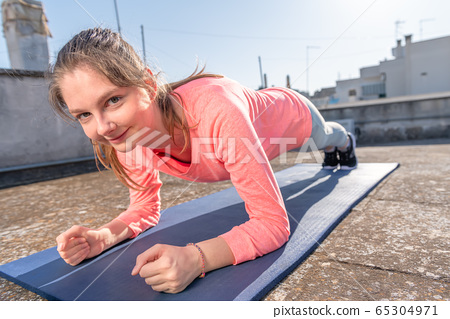 Young girl is doing plank on the mat on the roof 65304971