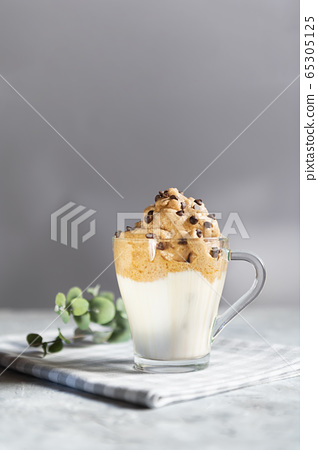 Dalgona frothy coffee in a transparent glass cup 65305125