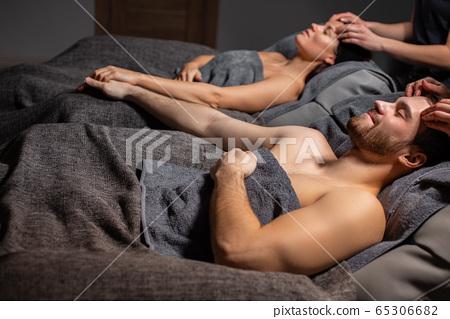happy couple lying on massage desks in spa salon 65306682