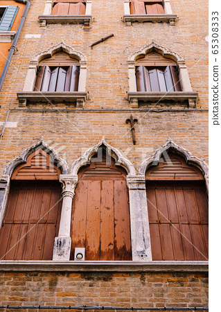 Windows of Venice are a building of several floors, made of red brick, three windows with brown shutters at bottom, two windows with wooden shutters-screen, stone columns and a sharp top by window 65308333
