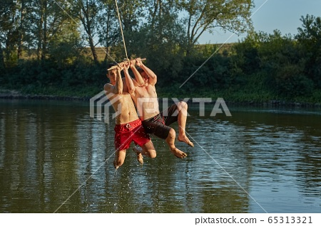 Guys jumping in a river 65313321