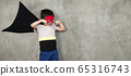 The boy dressed up in a superhero outfit, pretending to fight in studio.Study concepts And development of young children. 65316743