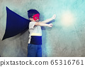 The boy dressed up in a superhero outfit, pretending to fight in studio,has light effect.Boy power concept And development of young children. 65316761