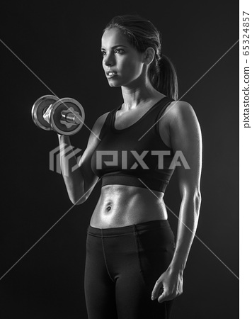 Beautiful woman exercising her biceps 65324857