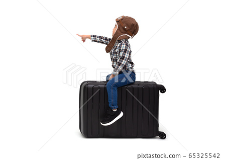 Happy kid Asian boy sitting on a black suitcase 65325542