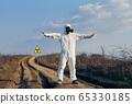 Environmentalist standing by ionizing radiation hazard symbol. 65330185