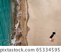 Areal top down view on sand beach and lifeguard tower on the island of Mallorca Mediterranean sea Port Adriano. Port Adriano, El Toro, Palma De Mallorca, Spain. Soft wave of blue ocean on sandy beach. 65334595