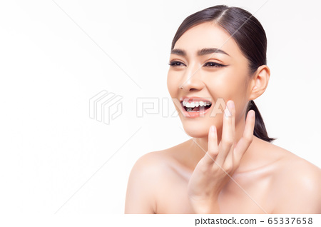 Beauty skin care. Asian woman get beautiful face skin, nice skin with happy. Attractive beautiful young girl look at copy space, smiley face and satisfied smooth face by touching her face. skin care 65337658