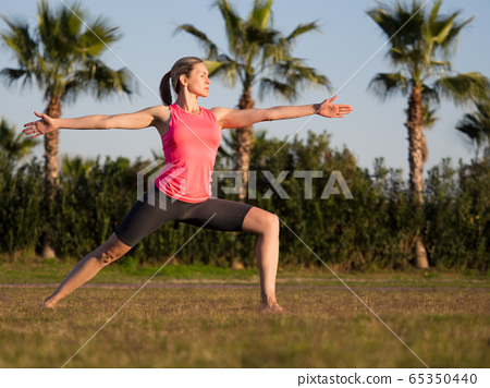 Warrior pose. Fit adult caucasian barefooted woman do yoga on the grass outdoor, selective focus. 65350440