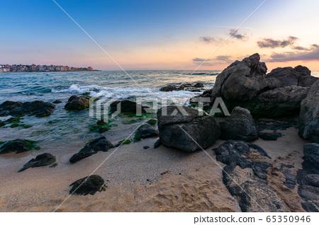 dramatic sunset on the sea shore. waves crashing 65350946