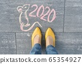 Top view on text and picture 2020 and pretty mouse, written on gray sidewalk with woman legs in feet in yellow shoes 65354927