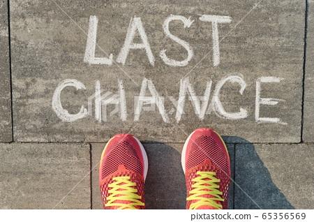 Text last chance written on gray sidewalk with women legs in sneakers, top view 65356569