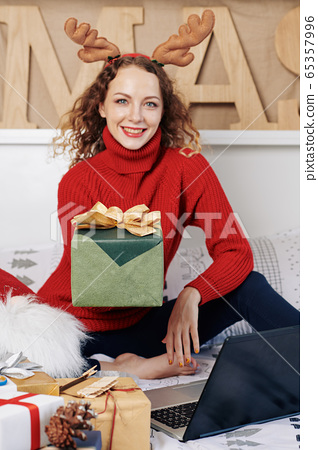 Woman giving Christmas present 65357996
