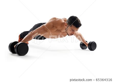 Bodybuilder doing wide push ups using dumbbells. 65364316