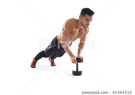 Muscular man doing push ups using dumbbell. 65364319