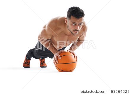 Shirtless bodubuilder doing push ups using basketball. 65364322
