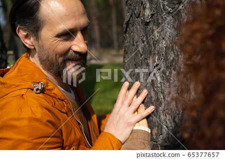 Happy married couple placing hands on tree 65377657