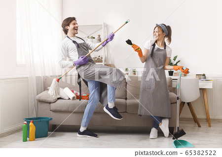 Joyful Couple In Aprons Playing With Household Tools While Tidying Flat 65382522