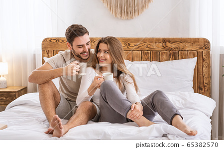 Happy couple in bedroom on bed and drinks from cups 65382570