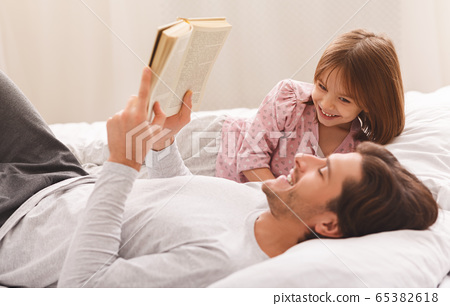 Young father reading book to little daughter, laying on bed 65382618