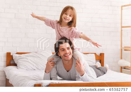 Positive little girl sitting on daddy shoulders, imitating airplane 65382757