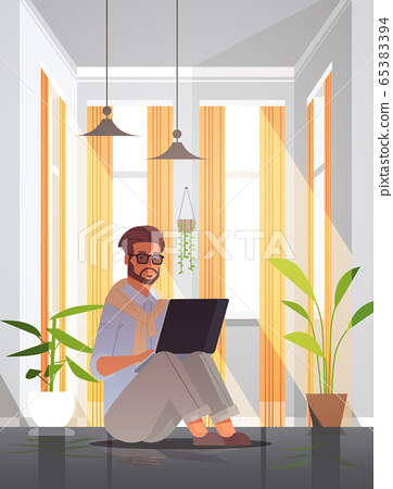 freelancer using laptop man working from home self-isolation coronavirus pandemic quarantine concept 65383394