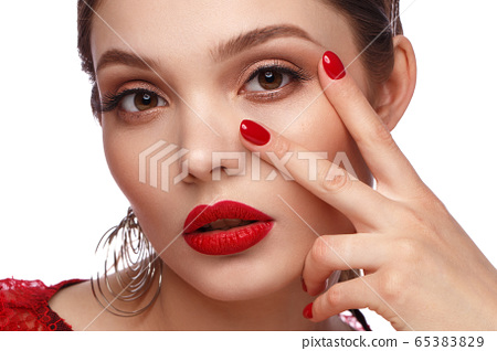 Beautiful girl in red dress with classic make-up and red manicure. Beauty face. 65383829